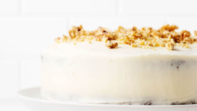 An angled photograph of a cake, which has been decorated with white frosting and chopped walnuts. It