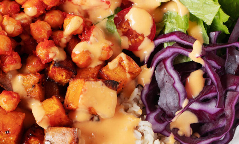 A close up, overhead image of a vibrant and colorful vegan chickpea burrito bowl. It