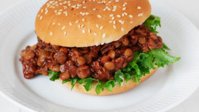 A sesame seed burger bun has been piled with BBQ lentils and a curly piece of bright green lettuce.